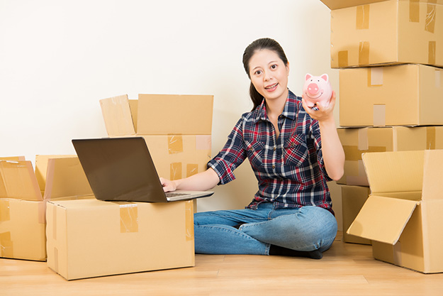 woman amongst boxes holding a piggy bank